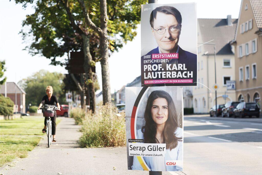 Wahlplakate von Karl Lauterbach und seiner Gegenkandidatin von der CDU, Serap Güter, hängen im Stadtteil Delbrück an der Strasse.